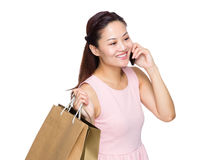 Young woman holding with shopping bag and talk to cellphone Stock Images