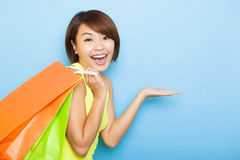 Young  woman holding shopping bags. Before blue background Stock Images