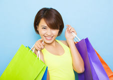 Young  woman holding shopping bags. Before blue background Royalty Free Stock Photography
