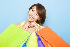 Young  woman holding shopping bags. Before blue background Royalty Free Stock Images