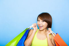 Young  woman holding shopping bags before blue background. Happy young  woman holding shopping bags before blue background Royalty Free Stock Images