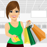 Young woman holding shopping bags and giving a credit card Royalty Free Stock Photos