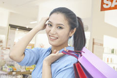 Young woman holding shopping bags with hand in her hair, looking at camera in a mall Royalty Free Stock Image