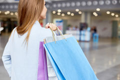 Young Woman Holding Shopping Bags in Mall Stock Photo