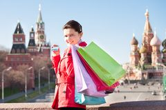 Young woman holding shopping bags and showing credit card Stock Image