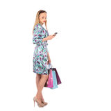 Young woman holding shopping bags and talking on a mobile Royalty Free Stock Images