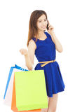 Young  woman holding shopping bags and talking on the phone. In studio Stock Photos