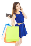 Young  woman holding shopping bags and talking on the phone. In studio Stock Images