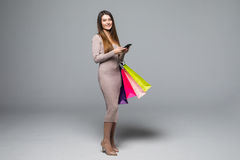 Young woman holding shopping bags and use mobile phone isolated on grey background Stock Image