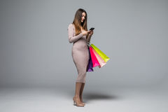Young woman holding shopping bags and use mobile phone isolated on grey background Royalty Free Stock Images