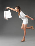 Young woman holding shoppping bag, tumbling Royalty Free Stock Photos