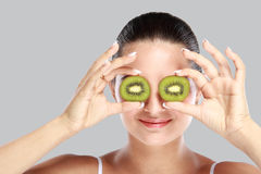 Young woman holding slices of kiwi in front of her eye Stock Photos