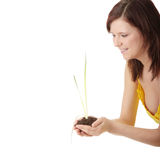 Young woman holding small plant and soil Stock Photo