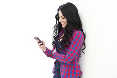 Young woman holding a smart phone while text messaging. Beautiful cute girl in a checkered shirt standing near a white wall and dials sms or internet use Royalty Free Stock Photography