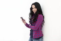 Young woman holding a smart phone while text messaging Royalty Free Stock Photo