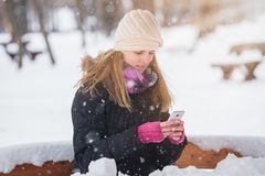 Young woman holding smartphone in the park during snowy day. royalty free stock photo