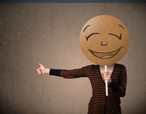 Young woman holding a smiley face board Stock Photography