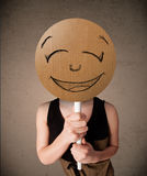 Young woman holding a smiley face board Stock Photo