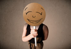 Young woman holding a smiley face board Stock Image