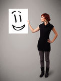 Young woman holding smiley face drawing. Attractive young woman holding smiley face drawing royalty free stock image