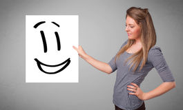 Young woman holding smiley face drawing Royalty Free Stock Photos