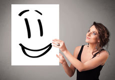Young woman holding smiley face drawing. Attractive young woman holding smiley face drawing royalty free stock images