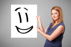 Young woman holding smiley face drawing. Attractive young woman holding smiley face drawing stock image