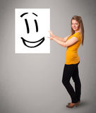 Young woman holding smiley face drawing Stock Photo