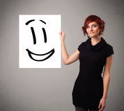 Young woman holding smiley face drawing Royalty Free Stock Images