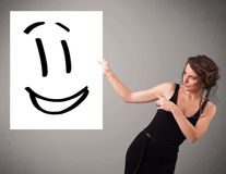 Young woman holding smiley face drawing Stock Images