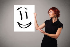 Young woman holding smiley face drawing Royalty Free Stock Image