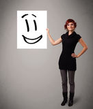 Young woman holding smiley face drawing Royalty Free Stock Photography