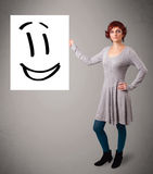 Young woman holding smiley face drawing Stock Photography