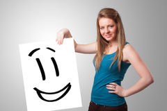 Young woman holding smiley face drawing. Attractive young woman holding smiley face drawing royalty free stock photography