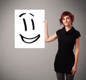 Young woman holding smiley face drawing. Attractive young woman holding smiley face drawing stock images