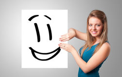 Young woman holding smiley face drawing. Attractive young woman holding smiley face drawing stock photo
