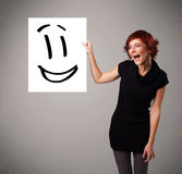 Young woman holding smiley face drawing. Attractive young woman holding smiley face drawing royalty free stock photo
