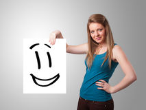 Young woman holding smiley face drawing. Attractive young woman holding smiley face drawing stock photos