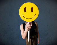 Young woman holding a smiley face emoticon Stock Image