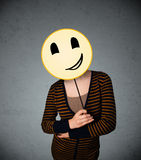 Young woman holding a smiley face emoticon Royalty Free Stock Photography