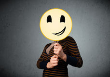 Young woman holding a smiley face emoticon. Young lady holding a yellow smiley face emoticon in front of her head Stock Image