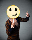 Young woman holding a smiley face emoticon Stock Images