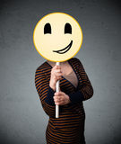 Young woman holding a smiley face emoticon Royalty Free Stock Photo
