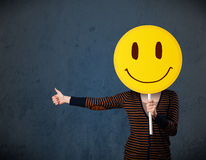 Young woman holding a smiley face emoticon Royalty Free Stock Photos