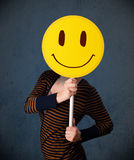 Young woman holding a smiley face emoticon Royalty Free Stock Images