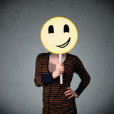 Young woman holding a smiley face emoticon Royalty Free Stock Image