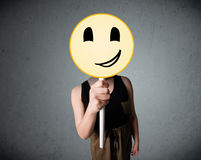 Young woman holding a smiley face emoticon Stock Photography
