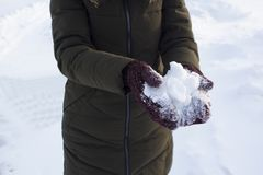 Young woman holding snow in her hands in mittens, winter, fun, joy, sports, recreation, children stock images