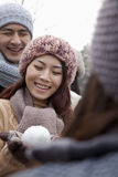 Young Woman Holding a Snowball and Smiling Royalty Free Stock Photography