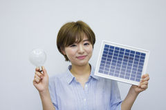 Young woman holding solar panel and light bulb Royalty Free Stock Images